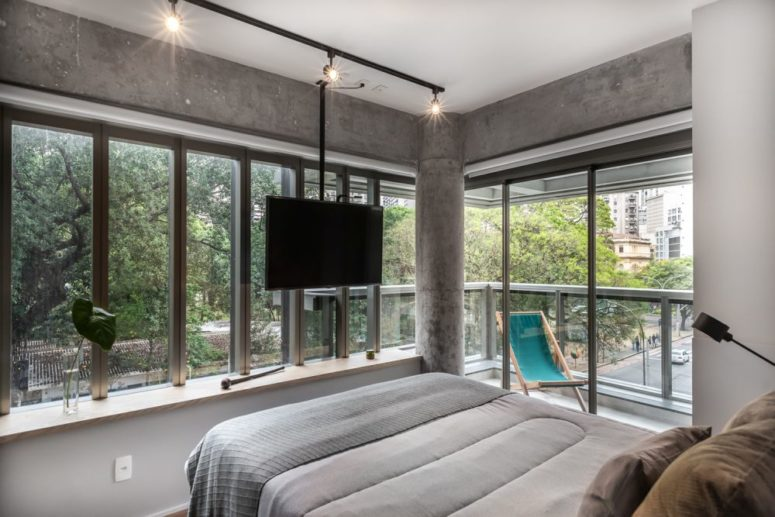 The master bedroom is done with concrete, there's a pillar and two glazed walls plus an access to the corner balcony