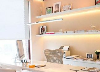 A Contemporary Neutrla Home Office With A Desk, A Cabinet For Storage, Lit Up Floating Shelves And A Large Window