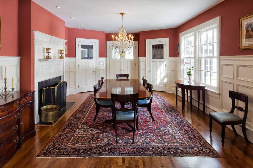 The pink upper walls of the dining room makes the white lower part of the walls stand out. These white elements are the doors, windows and mantle of the fireplace all connected with the white wainscoting that contrasts the dark hardwood flooring and dining set.