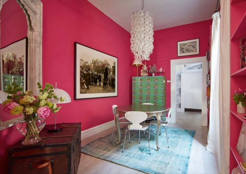 A large framed black and white photo is mounted on the pink wall by the modern stainless steel dining table that is surrounded by white modern chairs over a light green area rug that complements the avocado green dining room cabinet.
