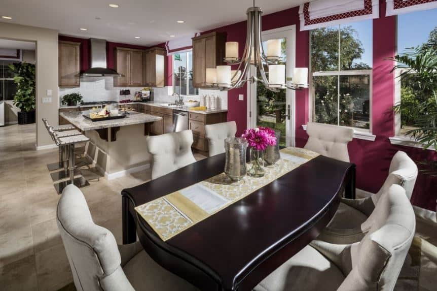 The small dining area is beside the kitchen under the same white ceiling and has the same white marble flooring that contrasts with the dark wooden dining table surrounded by light gray cushioned chairs that stand out against the pink walls.