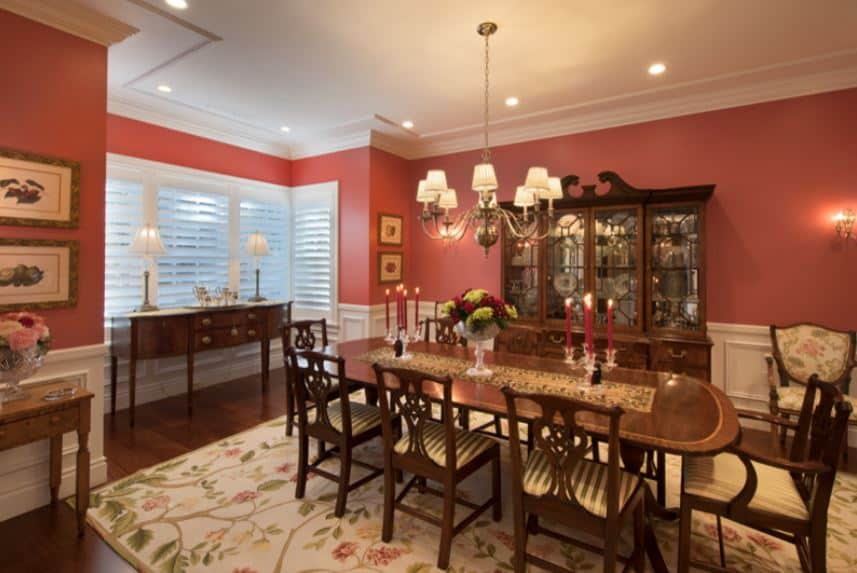 The charming area rug that covers most of the dark hardwood flooring has a design filled with tree branches and flowering plants that provide a colorful background for the wooden dining set and dining area cabinet against the pink wall.