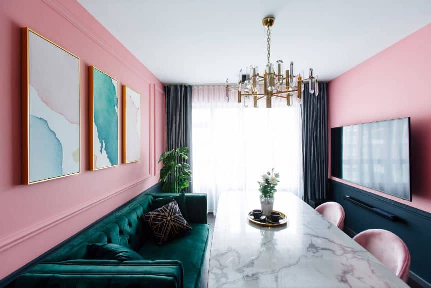 This dining room has two light pink walls. One side has a green velvet couch on it while the other has a green wainscoting. Both of these are flanking a long white marble dining table topped with a modern golden chandelier.