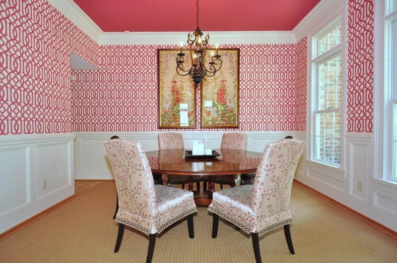 The matte pink ceiling that supports a wrought iron dark chandelier matches with the patterned wallpaper of the upper walls that provide a nice complex background for the white wainscoting, wooden round dining table and the cushioned chairs with floral slip covers.