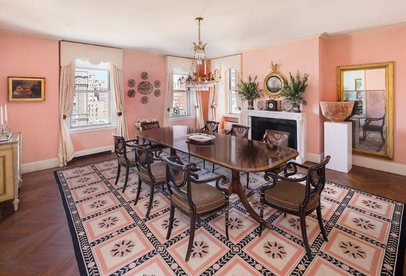 The dark hardwood flooring with a herring bone pattern is mostly covered by a patterned pink and black area rug that mirrors the light pink walls adorned with various artworks and a classic painting as well as a fireplace by the dining set.