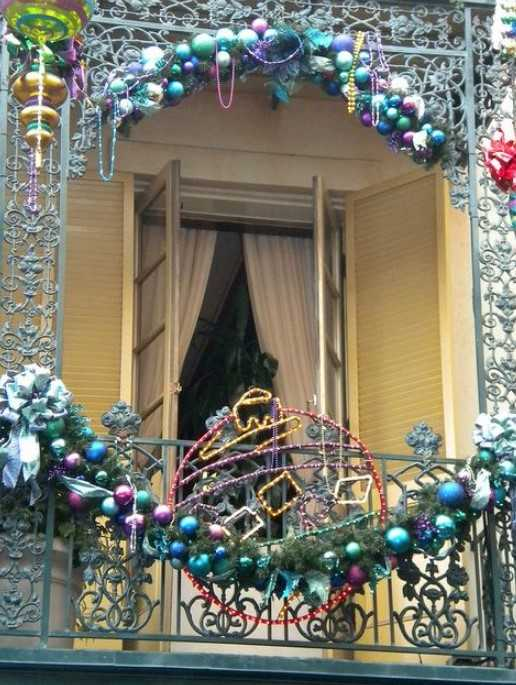 A Balcony Fully Decorated With Colorful Christmas Ornaments, Bows, Evergreens And Ornaments Made Of Lights