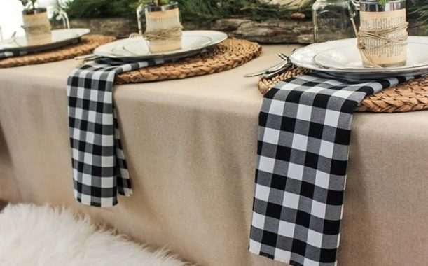 A Cozy Rustic Winter Table Setting With Plaid Napkisn, Woven Placemats, Evergreens, Candles And Antlers And Jars With Candles