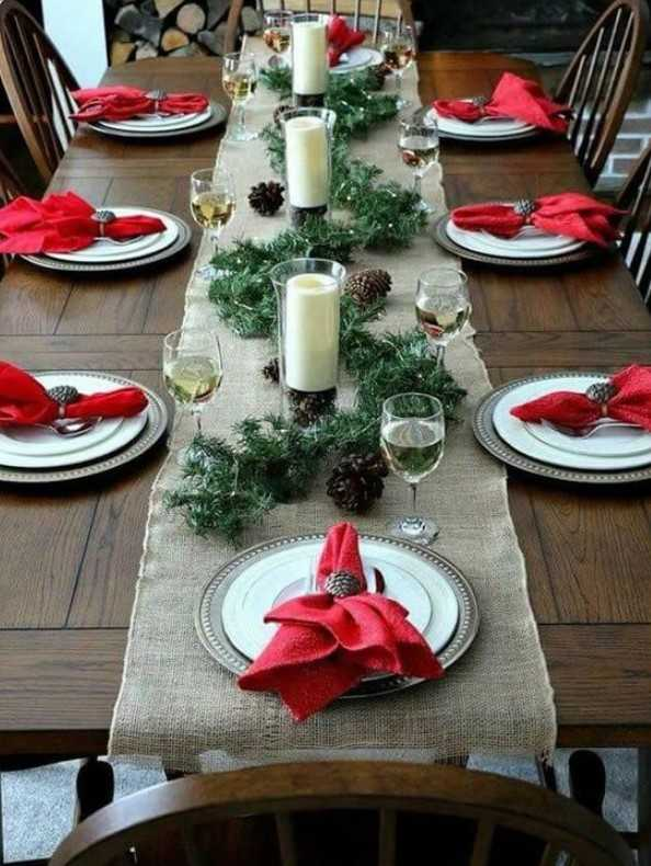 Bright Winter Tablescape With A Burlap Runner, Red Napkins, A Pinecone And Evergreen Runner Plus Candle
