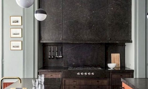 A Black Stone Kitchen With A Backsplash A Colorful Kitchen Island With A Stone Countertop And Pendant Lamps