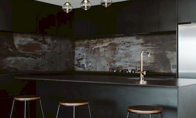 A Moody Black Kitchen With Sleek Cabinets A Rusty Metal Backsplash Pendant Lamps And Tall Stools