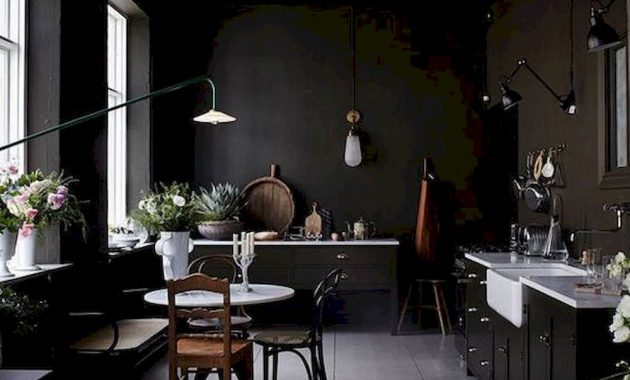 A Moody Vintage Kitchen With White Countertops Wall Lamps And Floral Arrangements