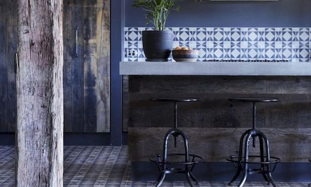 A Navy Kitchen With Blue Walls A Rug Printed Tiles A Rough Kitchen Island With A Stone Countertop Looks Chic