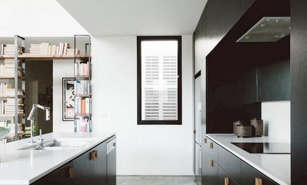 A Stylish Black Kitchen With Wooden Handles White Countertops And A Window To Fill The Space With Light