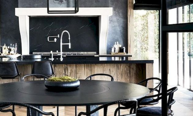An Elegant Moody Kitchen With A Wooden Kitchen Island With A Black Countertop And A Chalkboard Plus Pendant Lamps