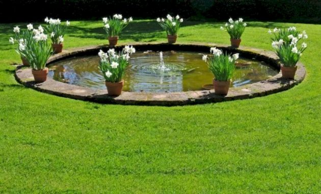 A Circular Garden Pond In The Center Of A Manicured Lawn