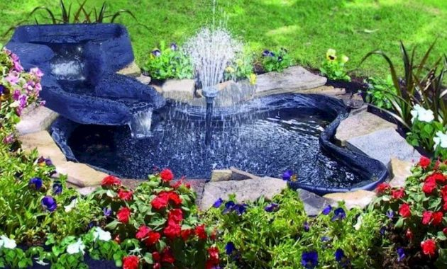 Simple Bright Blue Garden Pond With A Tall Center Fountain.