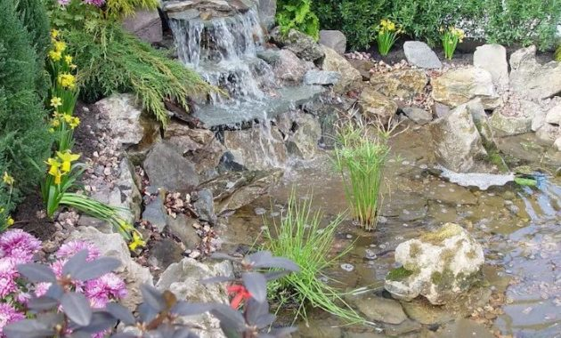 Stone Three Tier Waterfall Flowing Down From A Retaining Pond