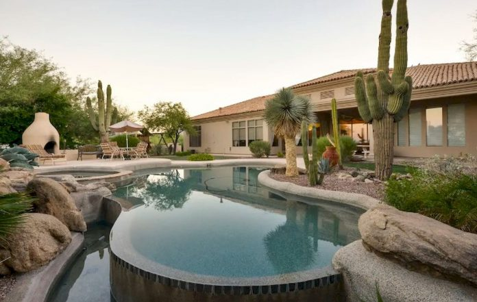 A Desert Home In Arizona With A Small Curvy Shaped Pool With Attached Hot Tub