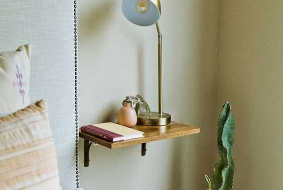 A Small Wooden Nightstand Attached To The Wall Can Hold Several Necessary Objects
