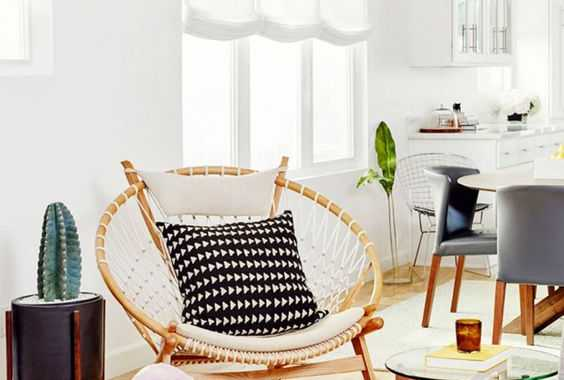 A Papasan Chair Styled In A Boho Way With Macrame And Monochromatic Pillows For A Boho Space