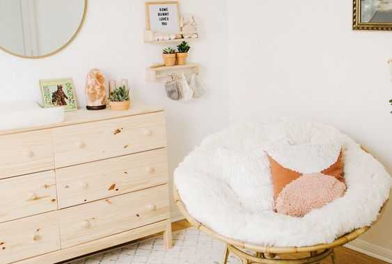 A Neutral Papasan Chair With A White Futon And Fringe Pillows Plus A Matching Footrest For A Neutral Nursery