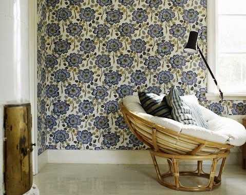 A Chic Reading Nook With A Blue Wallpaper Wall A Rattan Papasan Chair And Graphic Pillows