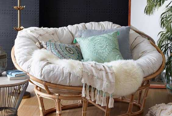 A Gorgeous Rattan Mamasan Chair With A Neutral Futon And Pastel And Printed Pillows For A Neutral Boho Space