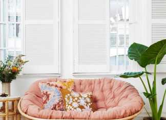 A Rattan Mamasan Chair With A Pink Futon Floral Pillows And Blooms And Potted Plants For A Boho Space