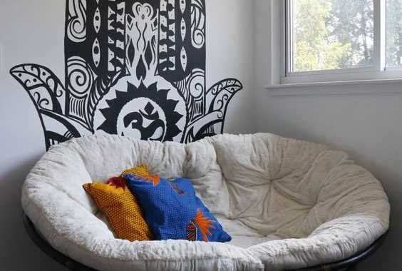 A Boho Nook With A Black Mamasan Chair Colorful Pillows And A Creative Decal On The Wall