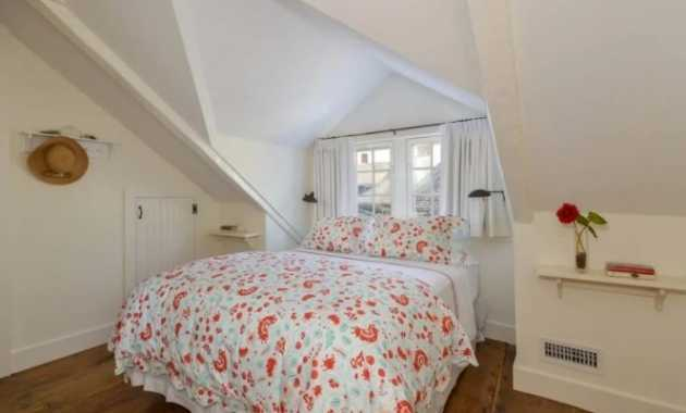 Cottage Style Bedroom Has A Bed With Colorful Floral Sheets