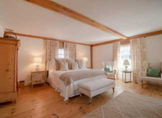 Cottage Style Primary Bedroom Matches Perfectly With Its Hardwood Flooring And The Large Wooden Cabinet