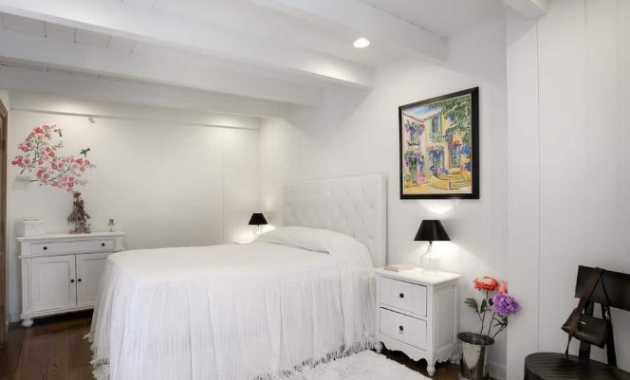 The White Wooden Ceiling Of This Cottage Style Bedroom Has Exposed Wooden Beams