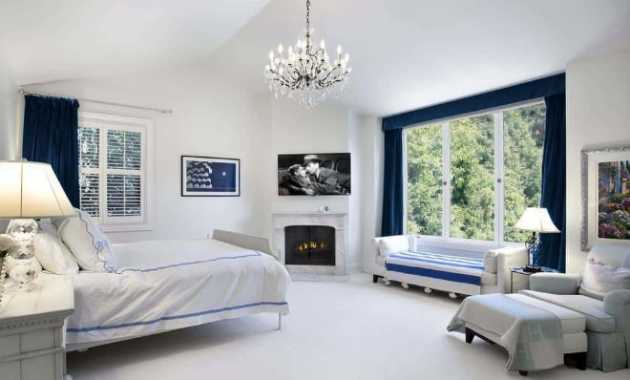 Bright Cottage Style Primary Bedroom Has A White Cathedral Ceiling White Walls And White Bed