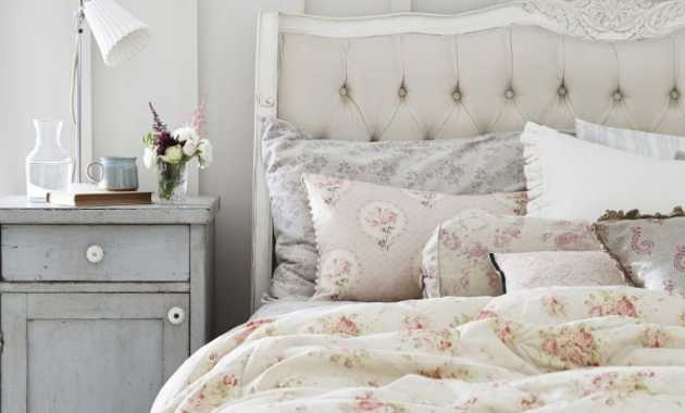 French Country Bedroom With Ditsy Bedding Layered With Floral Cushions And An Eiderdown